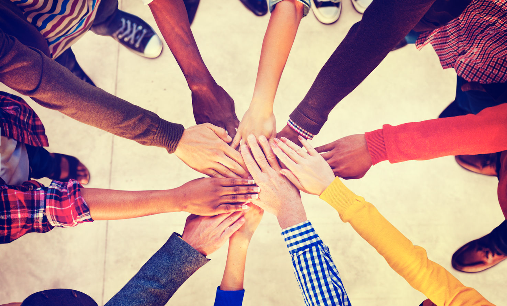 Diverse group of people joining hands