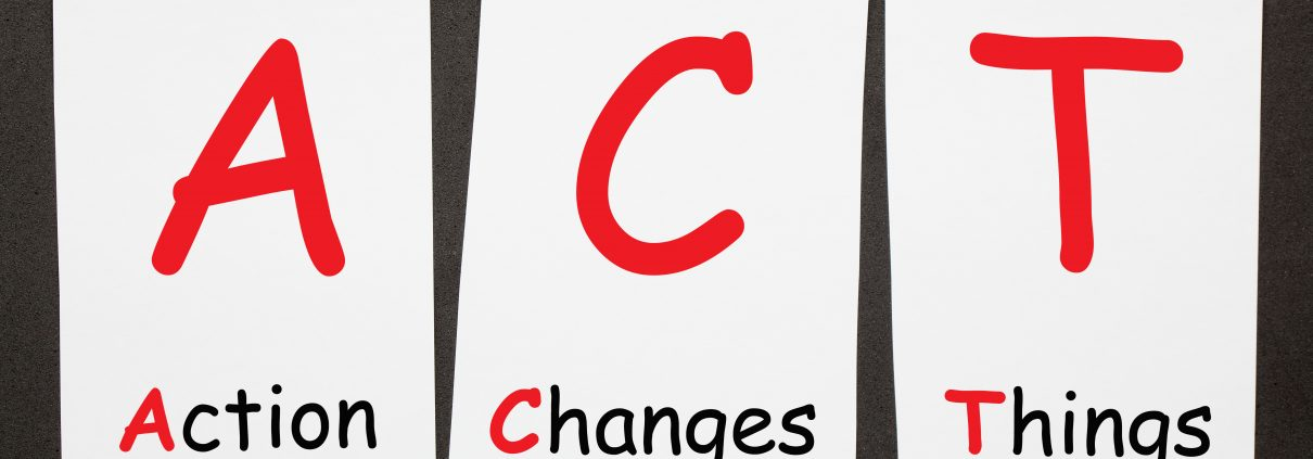 Action Changes Things (ACT) written on set stickers with clip hanging on a rope on black background.