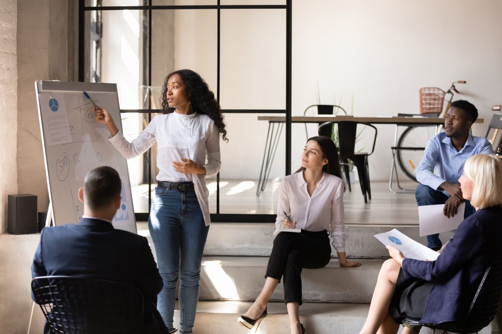 African businesswoman manager give whiteboard presentation at office meeting, female business coach presenter point on flip chart explain corporate strategy training diverse team at company workshop